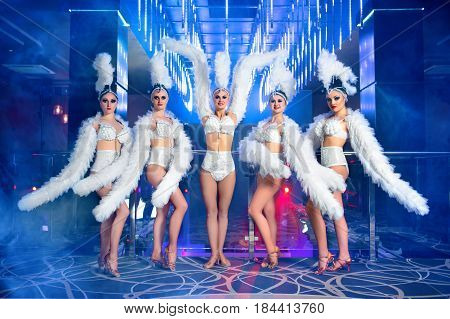 Shot of group of beautiful  go-go girls wearing white carnival costumes performing at the club dancing sexy sexuality sensuality seduction exotic erotic performers show time showgirls concept.