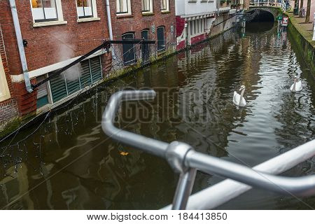 River canal and old street with bicycle parking lot in Dutch Delft old city