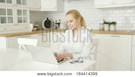 Young beautiful blonde wearing casual clothing and using laptop while sitting at table in modern white kitchen.