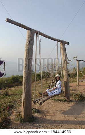 Thai Woman Sit And Play On Wooden Bench Swings Toy At Posing On Top Of Phu Pa Po Mountain Or Fuji Ci