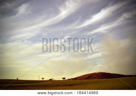 Wispy cirrus clouds over a sown field and hills at sunset in the NSW countryside, Australia