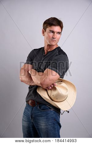the cute cowboy is crossing his arms with a cowboy hat.