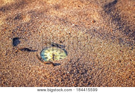 Still life - Antique rotten pocket watch buried partial in the sand