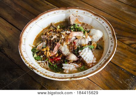 Special noodle spicy soup or noodles tom yam soup thai style with pork and seafood and soft-boiled egg and crispy wonton and other seasoning on wooden table at local restuarant in Loei Thailand