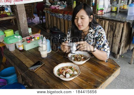 Thai woman shooting photo noodle tom yum seafood thai style before eating at local restaurant for writing blog on February 23 2017 in Loei Thailand