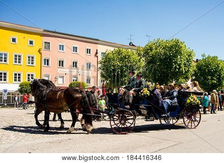 Tittmoning,Germany-April 30,2017: A horse carriage carrying women in vintage dresses arrives at the Annual St.George's parade