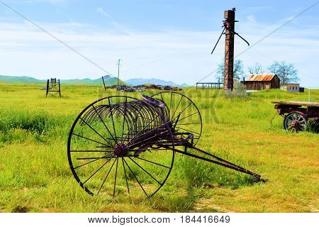 Abandoned antique farming equipment taken on a desolate forgotten landscape at a lush green prairie in the Carrizo Plain, CA