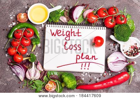 Fresh organic vegetables herbs and spices. Mix salad tomatoes chilli garlic and open blank notebook with plan eating. Weight loss concept. Products for boosting metabolism. Top view