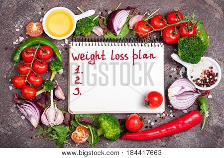 Fresh organic vegetables herbs and spices. Diet and healthy food concept. Mix salad tomatoes broccoli chilli garlic and open blank notebook with plan eating. Products for boosting metabolism. Top view