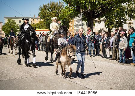 Tittmoning,Germany-April 30,2017: A little girl rides a pony at the annual St.George's parade