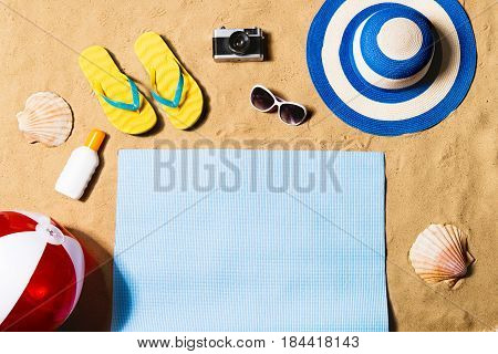 Summer vacation composition with pair of yellow flip flop sandals, hat, sunglasses, sun screen, beach ball and blue mat on a beach. Sand background, studio shot, flat lay, copy space.