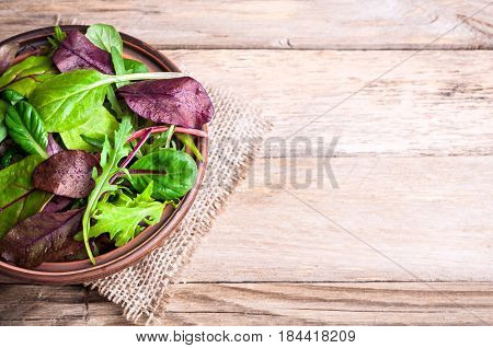 Mixed salad leaves on wooden rustic background with top view. Healthy food healthy lifestyle and diet concept. Fresh green salad with spinach arugula chard leaves lettuce. Copy space
