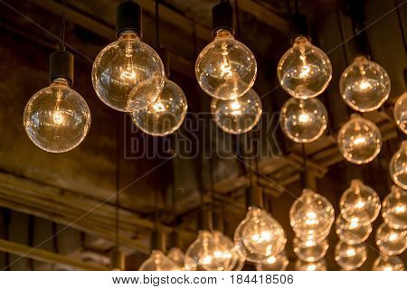 Group of Edison light bulbs hanged decoration from ceiling in department store.