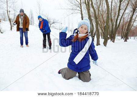 Happy family playing snowball fight in park