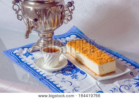 Professional bakery. Gorgeous white cheesecake, sprinkled with sweet crumbs. The background is  shiny samovar and cup with hot tea on blue kitchen towel