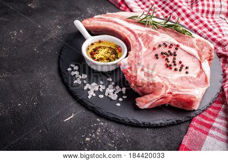 Raw meat with herbs oil and spices on dark background. Raw pork steak. Ingredients for cooking meat