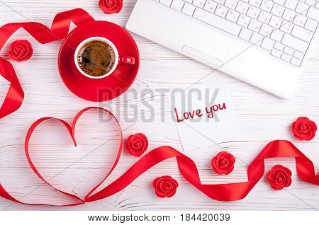 Valentines background with red heart coffee cup laptop and roses. Valentines Day greeting card. Female workplace. Top view