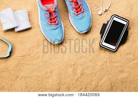 Blue sports shoes with pink shoelaces, earphones and smart phone, watch and white sweatbands laid on sand beach background, studio shot, flat lay. Copy space.
