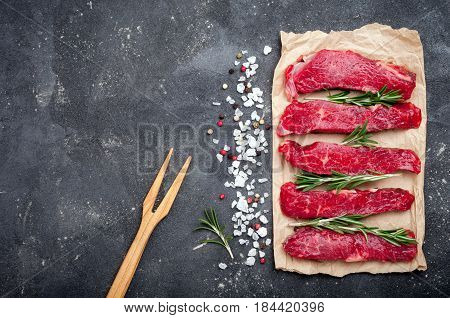 Raw meat on dark background. Raw beef stroganoff with herbs and spices. Cooking meat. Copy space. Top view