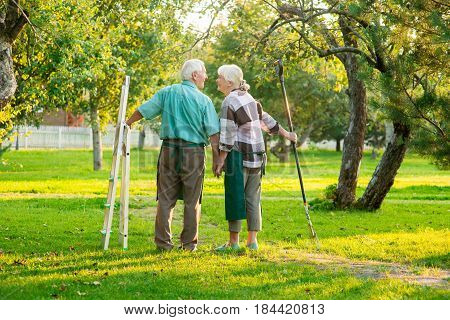 Senior couple holding hands, summer. Back view of two gardeners. Always here to help you.