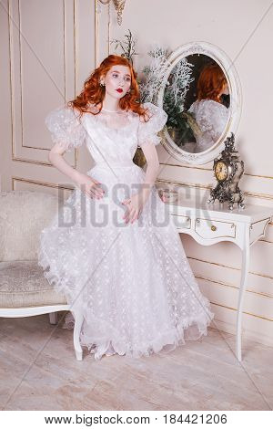 European woman with long red curly hair in a white vintage wedding european dress with white pearl earrings on her ears. Red-haired european girl with pale skin blue eyes a bright unusual appearance in the luxurious bedroom. European model