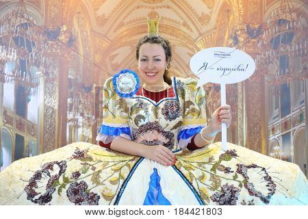 MOSCOW - DEC 4, 2016: Happy woman (with model release) poses in dress with cereals decoration at exhibition Foodshow in Sokolniki, text - i am queen, Mistral
