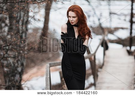 Portrait of glamorous slim girl with long red hair in black clothes. Slim woman in black slim dress and long black gloves posing on a background of winter autumn nature. Female street style. Beautiful elegant slim model