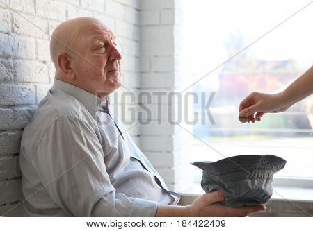 Senior man with hat asking for handout while sitting near brick wall. Poverty concept