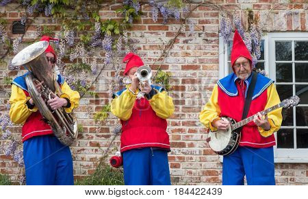 Downton, UK - 29 April 2017: Folk band dressed as garden gnomes entertain the crowds at the annual Cuckoo Fair in Downton, Wiltshire, UK.
