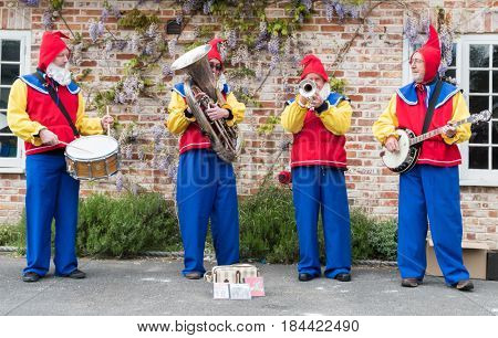 Downton, UK - 29 April 2017: Folk band dressed as garden gnomes entertain the crowds at the annual Cuckoo Fair in Downton, Wiltshire