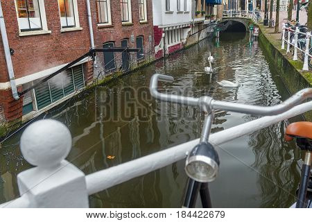 Water canal and city street with bicycle parking lot in Dutch Delft old city