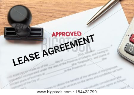 Approved lease agreement document with rubber stamp and calculator on wooden desk