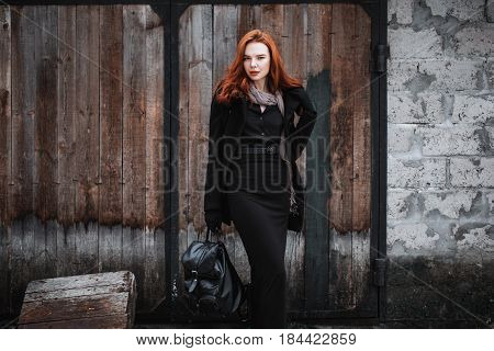 Striking grunge girl with long red hair in black clothes. A grunge woman in a black coat and backpack in hands posing on the grunge background of old grunge wall. Female street fashion grunge style. Beautiful elegant redhead grunge model