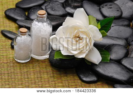 gardenia with salt in bottle and pile of stones on mat