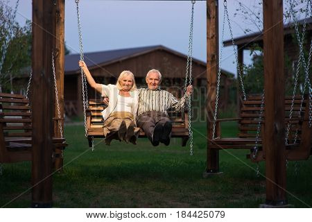 Elderly couple on porch swing. Man and woman smiling, evening. Two happy souls.