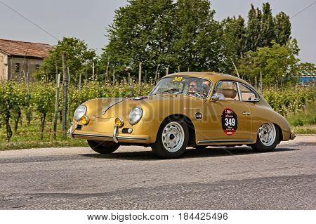 FORLI, ITALY - MAY 13: driver and co-driver on a vintage German car Porsche 356 Carrera 1500 GS/GT (1957) in classic car race Mille Miglia 2011, re-enactment of the old italian race (1927-1957) on May 13, 2011 in Forli, Italy