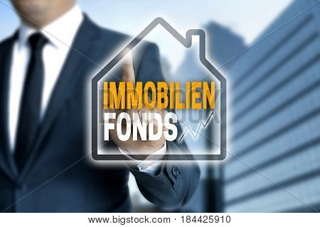 Immobilienfonds (in German Real Estate Fund) Touchscreen Is Operated By Businessman