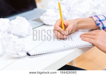 Woman Writing On A Notebook With Crumpled Paper Balls