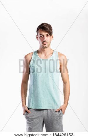 Handsome hipster fitness man in blue tank top shirt and gray shorts, hands in pockets. Studio shot on gray background.