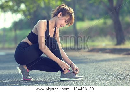 Closeup of woman tying shoe laces. Female sport fitness runner getting ready for jogging outdoors.