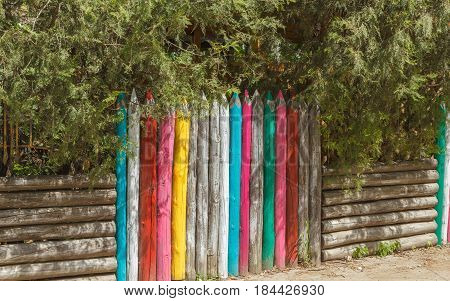 Wooden fence, made in the form of multi-colored pencils