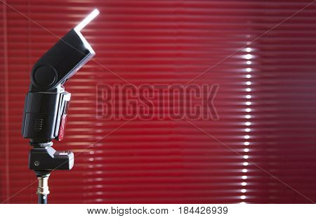 Speedlight flashgun shooting with white reflector over stand. Red blind as a background
