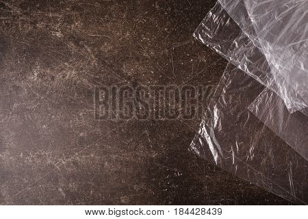 Cellophane bags on a dark marble background. Polute the nature. Eco concept