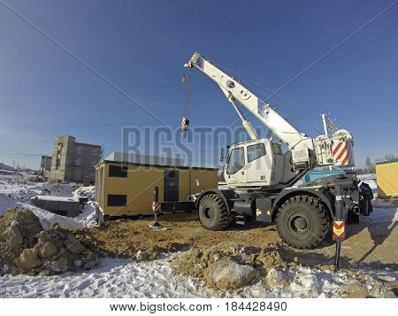 Mobile crane in work at a construction site winter. Crane on rubber wheels, with raised boom