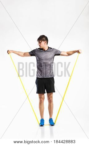 Handsome fitness man in gray t-shirt and black shorts working out with rubber band. Studio shot on gray background.