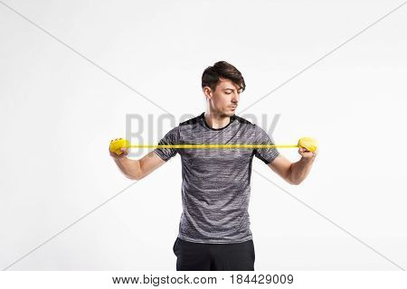 Handsome fitness man in gray t-shirt working out with rubber band. Studio shot on gray background.
