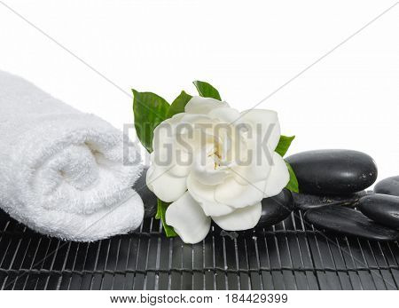 Rolled towel, black stones and gardenia on bamboo mat
