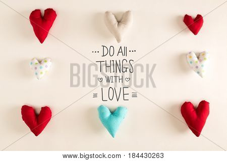 Do All Things With Love message with blue heart cushions on a white paper background