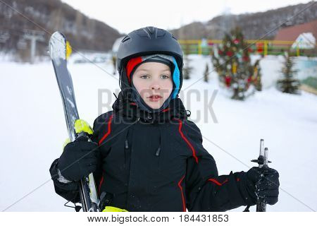 Boy in helmet with mountain ski stands in ski resort with mountains