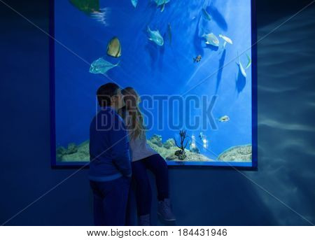 the father and daughter in oceanarium with fish